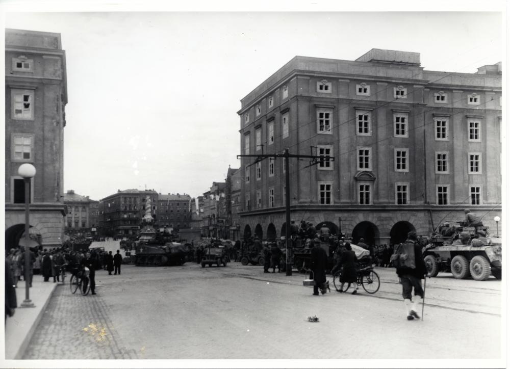 Der Fotograf der US-Armee zeigt die Bevölkerung im Moment der Ankunft amerikanischer Panzer in Linz. Die zahlreichen weißen Fahnen auf dem Hauptplatz im Hintergrund sind Zeichen der Kapitulation.