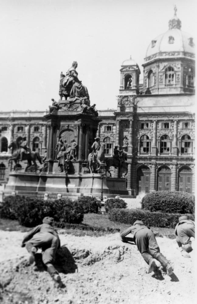 Hier stellen sowjetische Soldaten einen Kampf nach – rund um das Maria-Theresien-Denkmal mit Blick auf das Naturhistorische Museum. Die Perspektive gibt den BetrachterInnen das Gefühl, unter den vorrückenden Truppen zu sein.