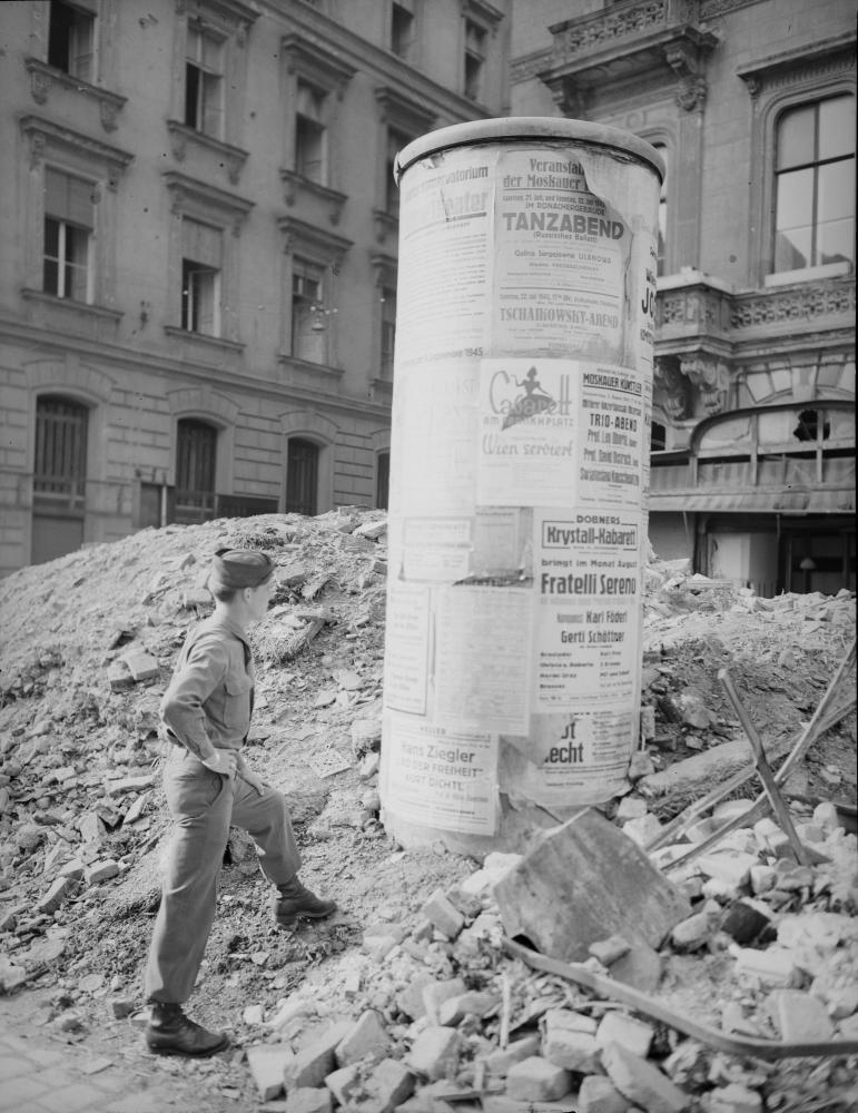 """Die Plakate auf der Litfaßsäule laden bereits zu Kabaretts, Tanzveranstaltungen und einem """"Tschaikowsky-Abend"""" ein. Angesichts des Schutts betont das Foto aber den Widerspruch zwischen Unterhaltung und Zerstörung."""