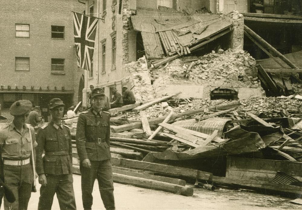 Schottischer Soldat der britischen Armee mit Wehrmachtssoldaten vor dem zerstörten Lienzer Rathaus.