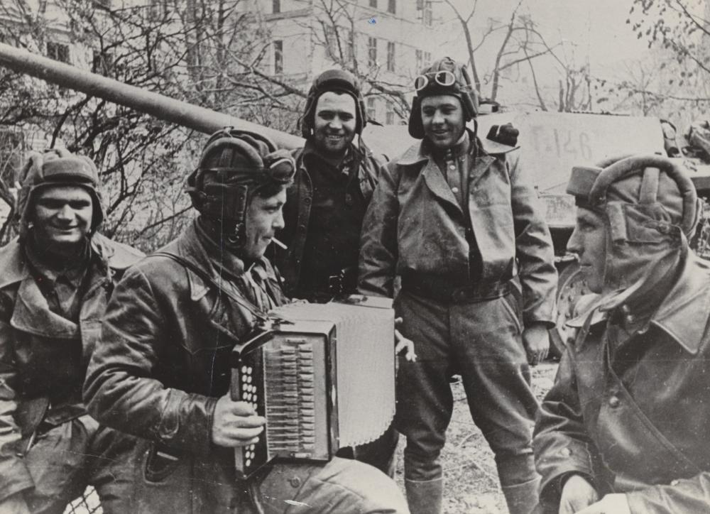 Dieses Bild wurde für die sowjetische Presse aufgenommen. Während die Abbildung großer Paraden für den Triumph des Staates standen, sollten Bilder wie dieses – die Freude der gewöhnlichen Soldaten in improvisierten Feiern – den menschlichen Aspekt des Kriegsendes zeigen.
