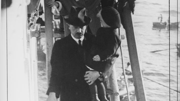 Zu sehen ist der frühere Kaiser Karl mit einem Kind auf dem Arm. Er verlässt über eine Treppe ein Schiff, gefolgt von kleinen Kindern. Seitlich sieht man das Meer.