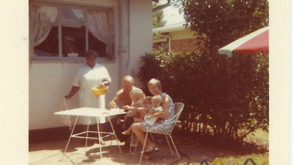 Familie Stangl auf einer Terrasse mit einem Schwarzen Dienstmädchen