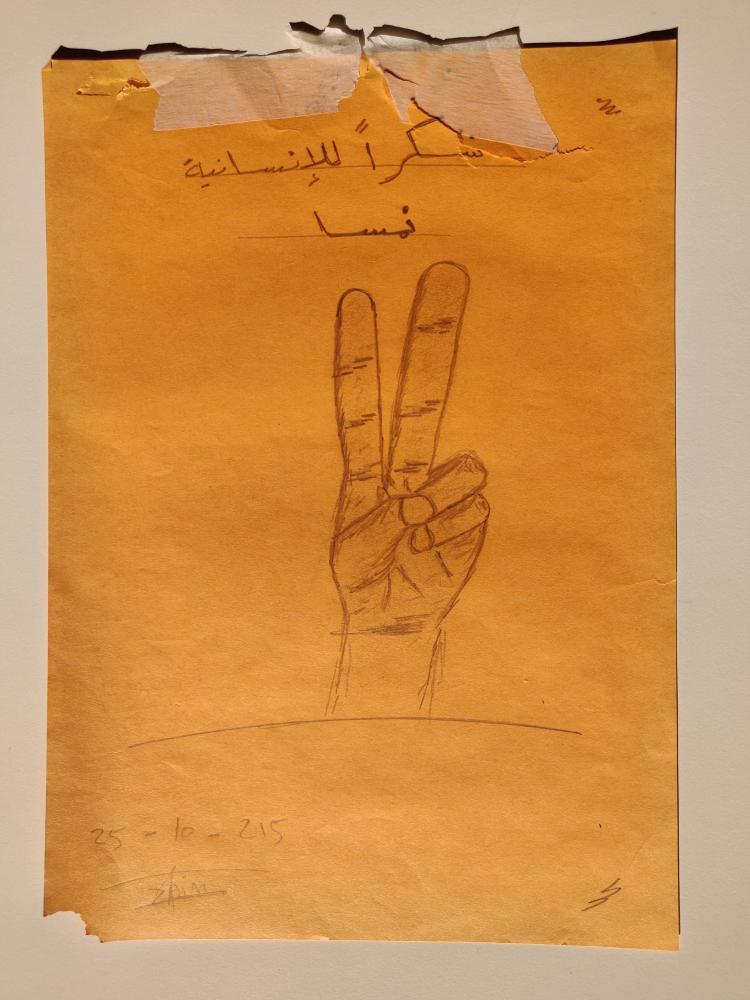 Zeichnung aus einem Transitlager in Wieselburg 2015. Über der Hand, die ein Peace-Zeichen bildet steht in Arabisch: